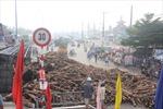 Lật xe tải, hàng chục tấn gỗ tràn xuống đường