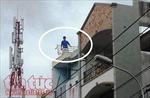 Chém vợ không được, thanh niên trèo lên sân thượng nhà hàng xóm đập phá tài sản