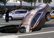 Đang chờ đèn đỏ, siêu xe 17 tỉ bất ngờ bị hố tử thần giữa phố 'nuốt chửng'